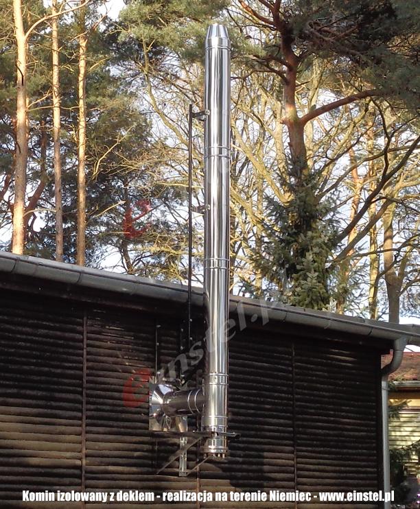 Zdjęcie obrazuje sposób instalacji komina z deklem. Komin przytwierdzony jest do drewnianej ściany. Konstrukcja wspomagana jest dodatkowym salowym stelażem dla lepszej stabilności.